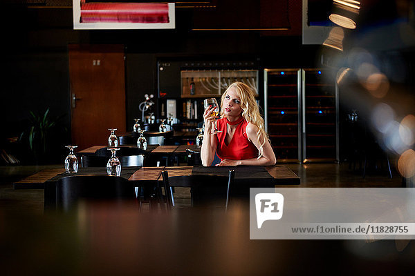 Glamouröse junge Frau mit langen blonden Haaren sitzt allein am Restauranttisch