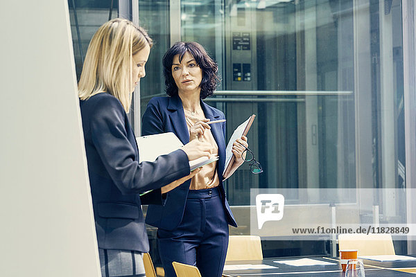 Two businesswomen having discussion in open plan office