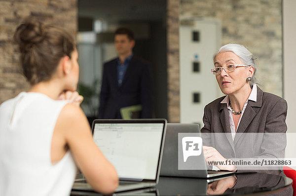 Reife Geschäftsfrau und Kollegin diskutieren über Bürotisch