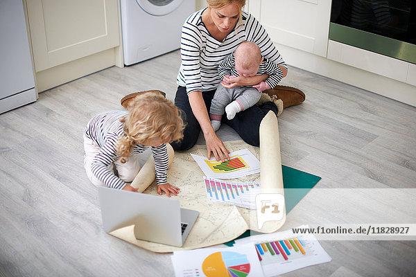 Frau hält kleinen Sohn im Arm  blickt durch Diagramme auf Küchenboden  junge Tochter hält Papier offen