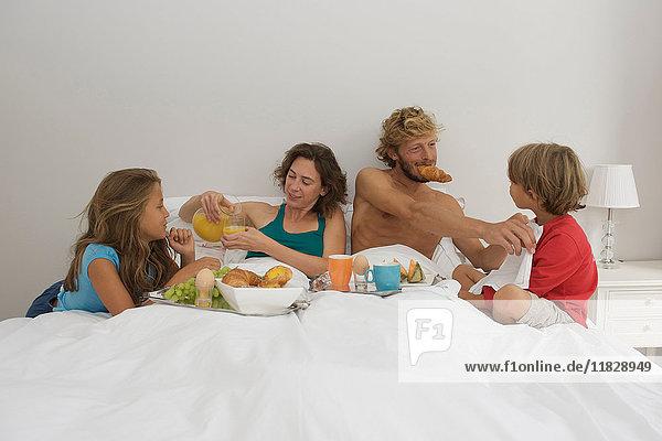 Junge Familie frühstückt im Bett