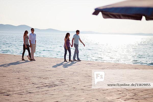 Paare gehen Hand in Hand auf dem Pier