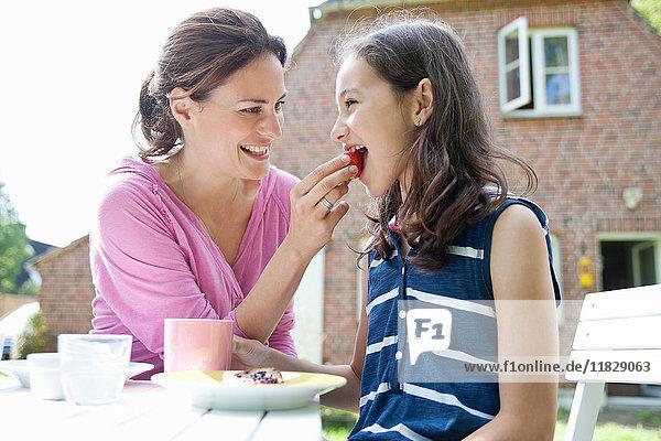 Mutter füttert Tochter im Freien