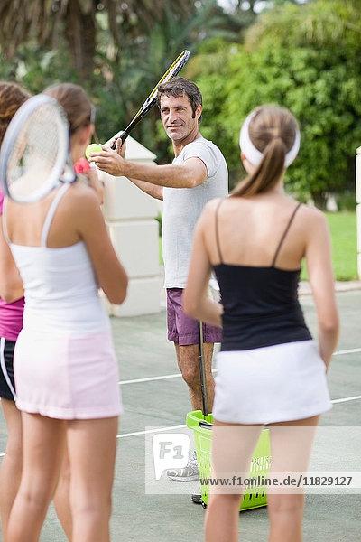 Tennistrainer demonstriert für Studenten