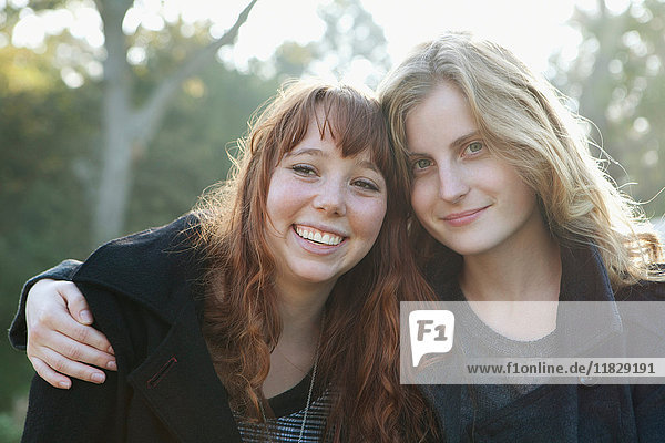 Teenage girls hugging outdoors