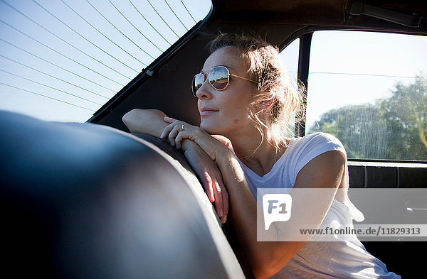 Woman in the back of a car  looking out