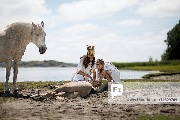 Girls petting horse on sandy beach