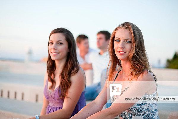 Frauen sitzen auf dem Pier im Freien
