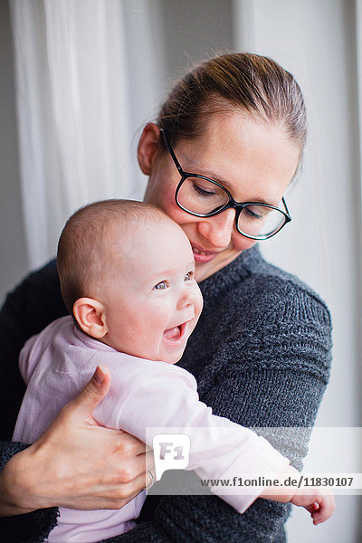 Mutter hält lächelndes Baby