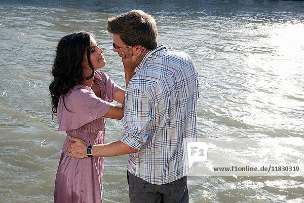 Paar küsst sich am Flussufer