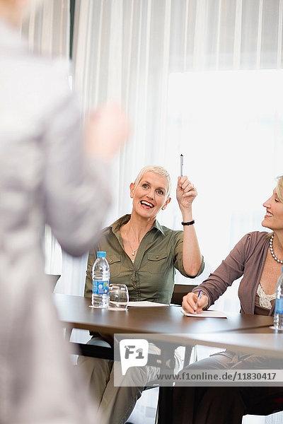 Geschäftsfrau hebt die Hand in der Sitzung