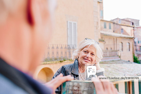 Über-Schulter-Ansicht eines männlichen Touristen  der seine Frau in der Stadt fotografiert  Siena  Toskana  Italien