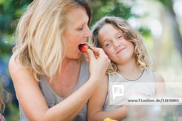Frau und Enkelin essen im Freien