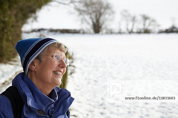 Glückliche Rentnerin in einem Schneefeld