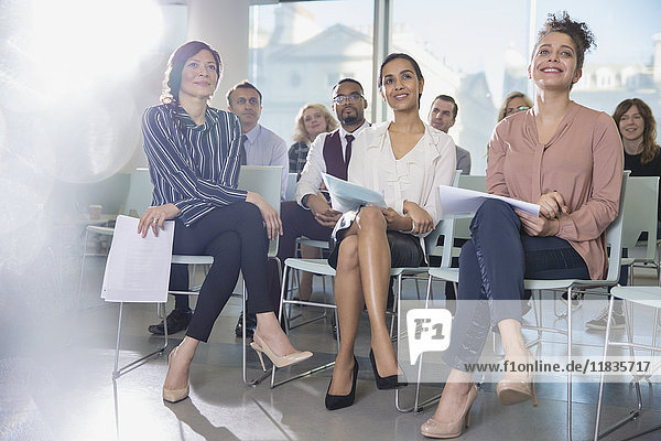 Aufmerksame Geschäftsfrauen beim Zuhören im Konferenzpublikum