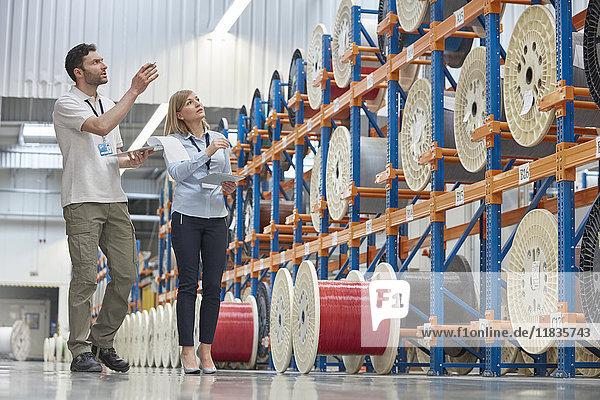 Männliche und weibliche Vorgesetzte bei der Bestandsaufnahme in der Glasfaserfabrik