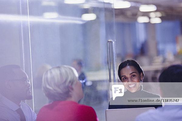 Lächelnde Geschäftsfrau mit Laptop in Konferenzraumbesprechung