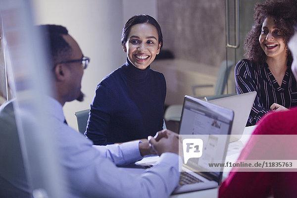 Lächelnde Geschäftsleute mit Laptops im Konferenzraum-Meeting