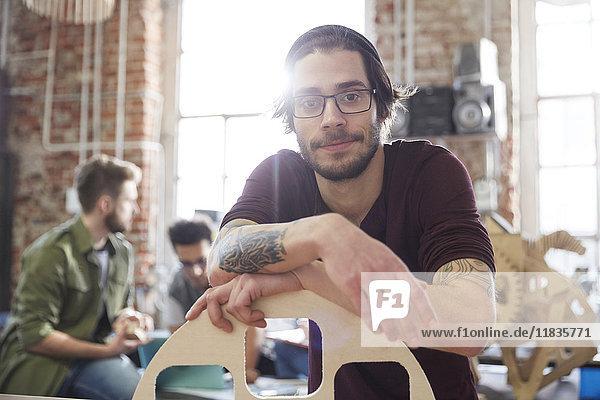 Porträt selbstbewusster Designer mit Tätowierungen am Prototyp in der Werkstatt