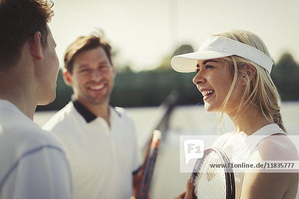 Tennisspielerinnen und -spieler im Gespräch auf dem Tennisplatz Tennisspielerinnen und -spieler im Gespräch auf dem Tennisplatz