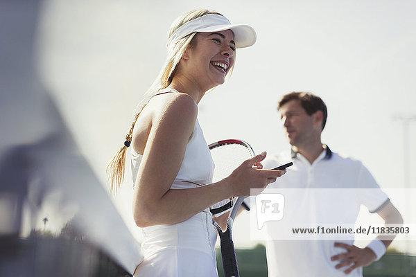 Lachende Tennisspielerin mit Handy und Tennisschläger