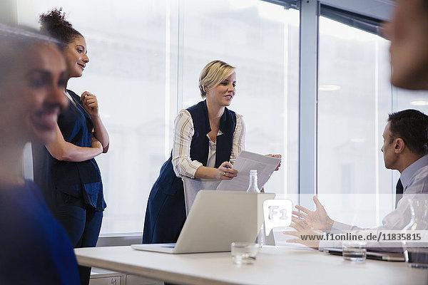 Geschäftsleute diskutieren Papierkram in Konferenzraumbesprechung