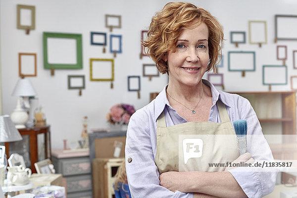 Portrait lächelnde reife Künstlerin im Kunstladen mit Bilderrahmen