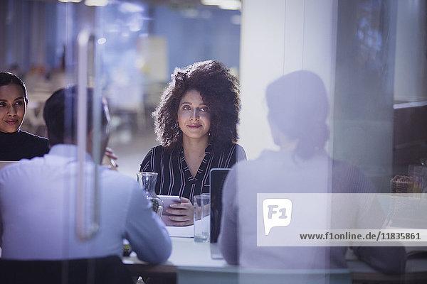 Geschäftsfrau beim Zuhören im dunklen Konferenzraum