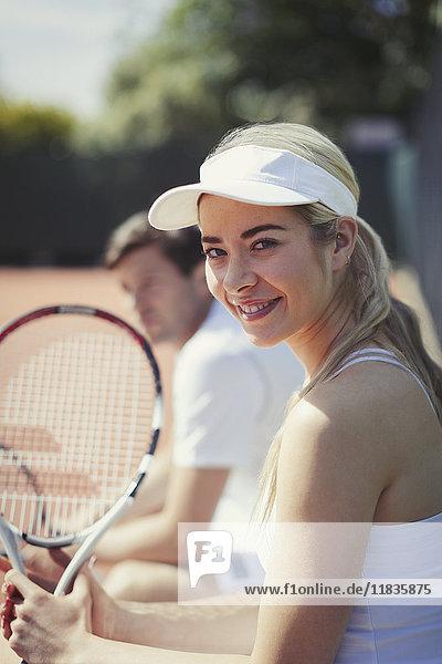 Portrait lächelnde  selbstbewusste junge Tennisspielerin mit Tennisschläger auf sonnigem Tennisplatz Portrait lächelnde, selbstbewusste junge Tennisspielerin mit Tennisschläger auf sonnigem Tennisplatz