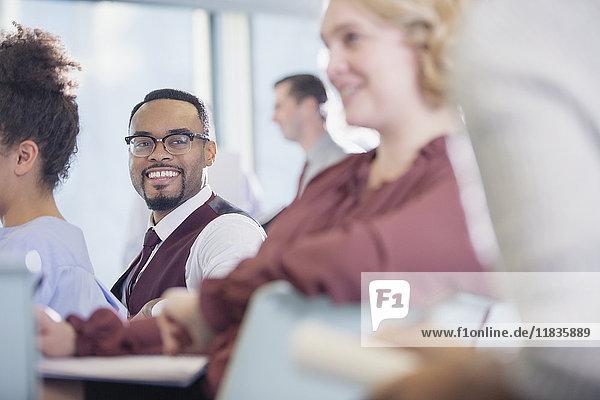 Lächelnder Geschäftsmann beim Zuhören im Konferenzpublikum