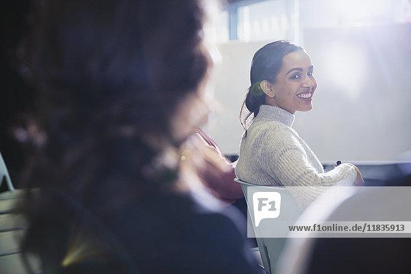 Lächelnde Geschäftsfrau dreht sich um und blickt zurück ins Konferenzpublikum.