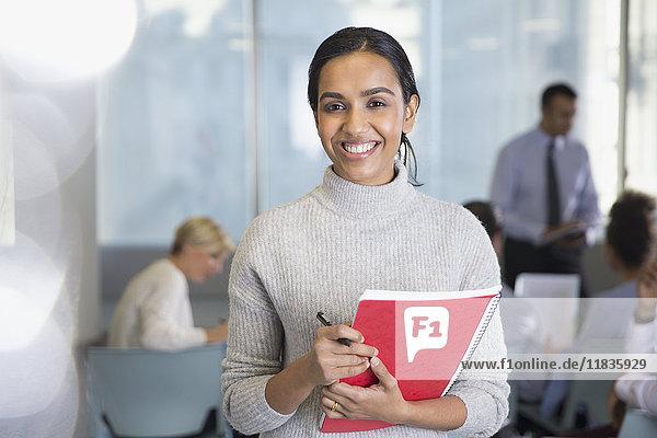 Portrait lächelnde Geschäftsfrau mit Notizbuch im Konferenzpublikum