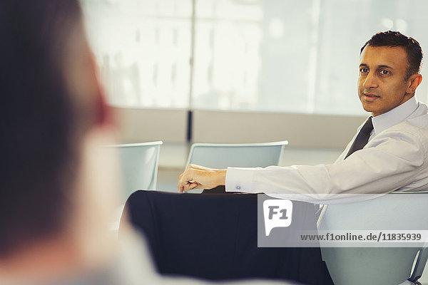 Geschäftsmann beim Drehen  Rückblicken und Zuhören im Konferenzpublikum