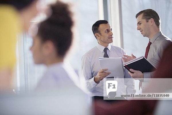 Geschäftsleute sprechen im Bürofenster