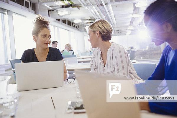 Geschäftsfrauen beim Reden  Arbeiten an Laptops im Büromeeting