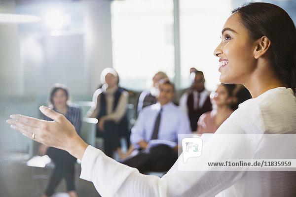 Lächelnde Geschäftsfrau leitet Konferenzpräsentation