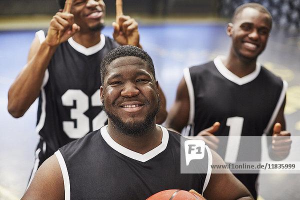 Portrait lächelndes  selbstbewusstes junges Basketballer-Team in schwarzen Trikots  das den Sieg feiert.