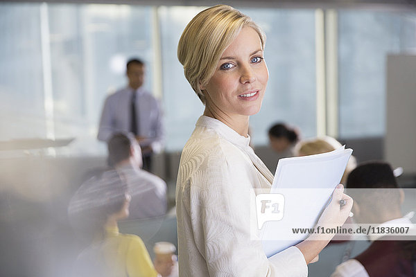 Portrait smiling businesswoman with paperwork in conference room meeting