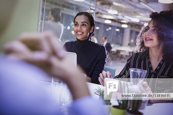 Lächelnde Geschäftsfrauen hören im Konferenzraum zu