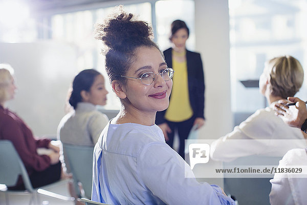 Porträt einer lächelnden  selbstbewussten Geschäftsfrau  die sich im Konferenz-Publikum umdreht.