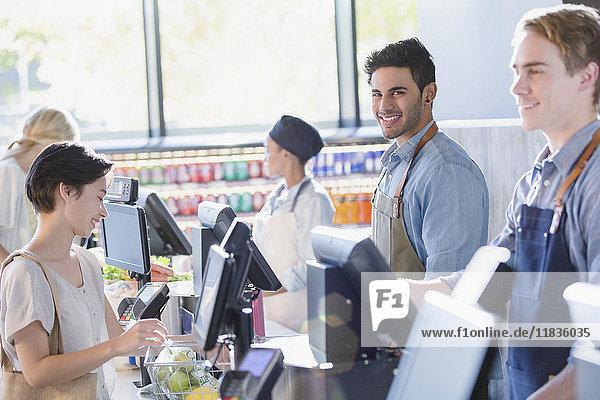 Portrait smiling  confident young male cashier working at grocery store market checkout