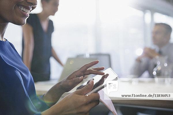 Nahaufnahme einer lächelnden Geschäftsfrau mit digitalem Tablett im Konferenzraum Meeting