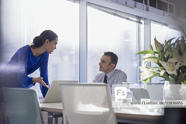 Geschäftsleute  die am Laptop arbeiten und sich im Konferenzraum unterhalten