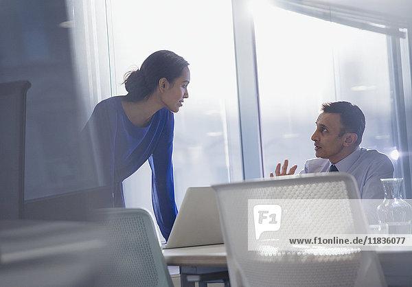 Geschäftsmann und Geschäftsfrau mit Laptop  im Büro sprechend