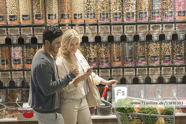 Young couple using cell phone  grocery shopping in market