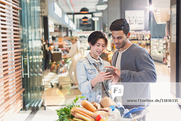 Young couple using cell phone in grocery store market