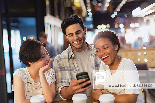 Young friends using cell phone  texting and laughing at cafe