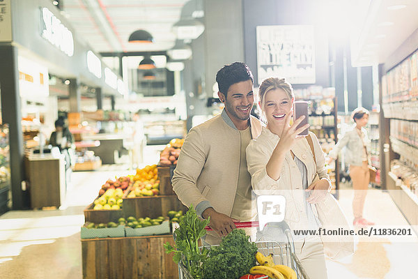 Smiling young couple taking selfie in grocery store market