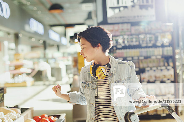 Young woman with headphones browsing  grocery shopping in market
