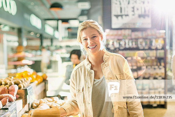 Portrait smiling young woman grocery shopping in market